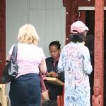 Maorisk kvinna visar vävning med fibrer från harakeke och wharariki